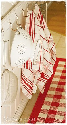 In my kitchen... Strainers on hooks, red check rug from Ikea