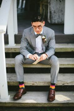 Countryside groom in grey suit and bow tie, with statement dress socks!