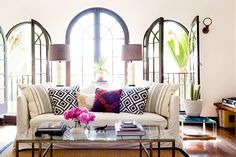 Bright living room with open windows, off-white sofa, black, white, and red patterned pillows, and glass coffee table