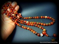"Old Buddhist Asian Satin Finish Carnelian Agate 108 bead Prayer Mala on silk with tassel  The mala consists of 108 main 8mm beads and measures 35 inches in length not including the 1 1/2 "" tassel and two beads. The circumference of the beads is approximately 1"", the length of each bead is 1/4"". The mala weighs 2.872ounces.  by TemplesTreasureTrove, $150.00"