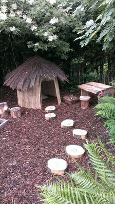 A fresh take on a children's play house - a DIY rustic roundhouse made from natural reed screening (walls) and a brushwood screening roof. The area also features a wooden table and chairs made from logs and timber planks. This is our natural children's ou Outdoor Play Spaces, Kids Outdoor Play, Kids Play Area, Outdoor Learning, Backyard For Kids, Rustic Backyard, Eyfs Outdoor Area, Natural Play Spaces, Kids Play Spaces