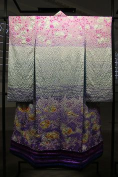 Mask - Memories of silk miracle This carefree kimono depicts mandarin ducks playing on the shore in the radiant spring sunshine. In Japan, Mandarin has long been considered symbols of fidelity and joy, and created several Kubota kimono using this image.