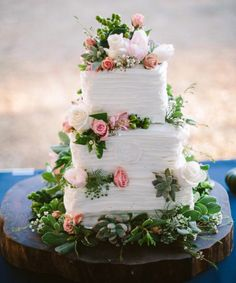 3 tiered square wedding cake decorated with a crum catcher design, adorned with pink roses, tulips seeded eucalyptus, succulents and wax flower. Cake designed by Flowers by the Bunch