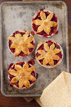 Miniature strawberry rhubarb pies topped with flower-shaped pie crust.