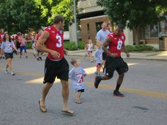 Taylor Martinez and Ameer Abdullah at the Uplifting Athletes 5K/1 Mile Fun Run July 2013.  Too cute!