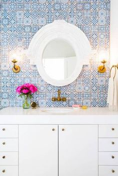 White and blue bathroom features a wall clad in blue Moroccan tiles, Fez Blue Vintage Moroccan Victorian Encaustic Effect Pattern Wall & Floor Tiles, lined with a white lacquered washstand adorned with aged brass knobs topped with thick white quartz and p Blue Moroccan Tile, Moroccan Bathroom, White Bathroom, Moroccan Rugs, Boho Bathroom, Moroccan Tile Backsplash, Feminine Bathroom, Mosaic Bathroom, Moroccan Interiors