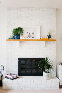 A 5-minute home makeover that will drastically change your living room. White painted brick fireplace with art print centerpiece.