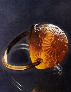 René Lalique Art Deco Glass 'Daisy' Ring,1920. Gold ring set with a sherry-colored glass bead with daisy motif. Source: The Jewellery of Rene Lalique, by Vivienne Becker