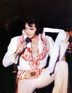 Elvis - kneeling close to the fans; wearing the cross pendant; red phoenix jumpsuit