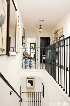 Sikes and Griffin added custom wrought-iron railings that define the upstairs hallway.   - HouseBeautiful.com