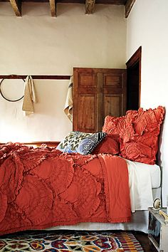 Coral, distressed wood, colorful rug and cream color walls.