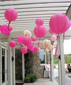 Pink chinese lanterns hanging from the pergola