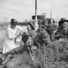 A nurse working with the Belgian resistance bandages a minor wound for a British soldier in Antwerp, 11 September 1944.