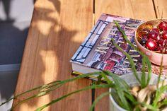 Een zeer eigentijdse tuintafel van het merk Suns. De tafel heeft een teakhouten blad van brede planken en een onderstel van gepoedercoat aluminium van hoge kwaliteit.