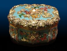 VERY CLOSE, Gloriously Gem Encrusted Oval Shaped German Snuffbox. Glass, Gold, Large Diamonds, Rubies, & Emeralds on a Blue Enamel Ground. Berlin, 1765. Metropolitan Museum of Art Collection, The Lehman Collection, NYC. Snuffbox photo & background photo by Christian Orlov. I isolated & retouched the snuffbox image onto this suitable background, by adjusting the lighting & creating shadows, making it appear as though the jewel was photographed in situ. (C) 2015 Christian Orlov. No. 14.