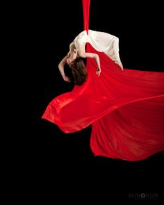 imagine this NOT being red. great image of aerialists blowing with the other pieces of hanging linens
