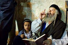 Jewish grandfather teaches his grandson prayers at the Wailing Wall in Jerusalem Israel.
