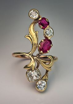 Antique Art Nouveau Ring is designed as a stylized spray of flowers with green gold chased leaves, set with diamonds and natural rubies. Made in Moscow between 1899 and 1908.