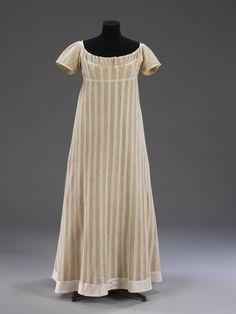 """Dress: ca. 1812, English, knitted fabric, cotton (probably), silk ribbon, lined with silk. """"Dress made of warp-knitted fabric, probably cotton. With a pattern of alternating stripes of close 'plain' knitting and open work. The sleeves and a band inserted around the neck are also in knitted cotton with a smaller pattern of alternating plain and open work."""""""