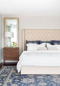 Blue and white decor in master bedroom. This stunning cream and blue bedroom features a linen tufted wingback bed dressed in white bedding and blue pillows next to a French nightstand. The headboard is from Restoration Hardware. Blue Master Bedroom, White Bedroom, Blue Bedrooms, Master Bedrooms, Blue And Cream Bedroom, Blue And White Bedding, Luxury Bedrooms, Master Suite, Bedroom Furniture