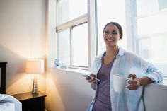 Smiling woman drinking coffee and texting at window