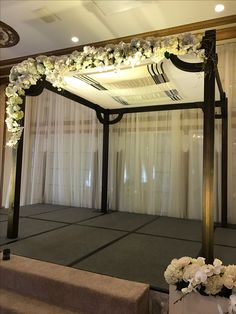 Clean and simple in design. Dark wood with curved corbels. This Chuppah has a clean and simple wedding florals in asymmetrical design.