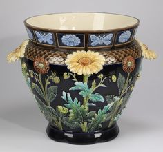 """Monumental Choisy le Roi majolica jardiniere, circa 1880, having a flared band at the neck with alternating bas relief butterflies and flowers in light blue on a cobalt blue ground, the shoulder having a brown fish scale band and the tapering body having high relief sunflowers and daisies on naturalistic stems, the whole resting on a circular scalloped base with a black transfer mark 'B H Choisy le Roi,' 24""""h x 28""""dia. Condition: Tip of one leaf on one of the sunflowers is missing."""