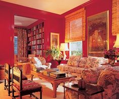 "Mario Buatta--The library's red walls ""make it a warm evening room away from all the white,"" Buatta says. Hyde Park Antiques low table. The Jean-Michel Frank cane chairs with Clarence House seat cushion fabric."