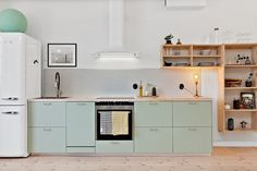 kitchen with mint green cabinets and open box shelving