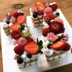 número de hojaldre relleno con crema diplomática, decorado con frutos rojos y fresas.