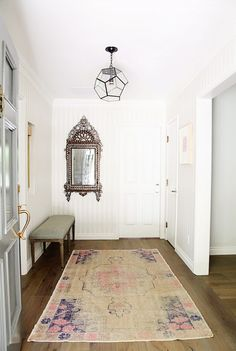 Entryway with faded oushak pink and purple and beige rug, ornate Venetian-like mirror, Louis bench, white beadboard walls, gray front door with brass hardware, gorgeous wood floors