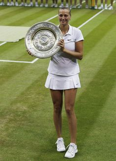 Petra Kvitova of Czech Republic holds the trophy as she poses for photographs after winning the women's singles final defeating Eugenie Bouchard of Canada at the All England Lawn Tennis Championships in Wimbledon, London, Saturday, July 5, 2014. (AP)