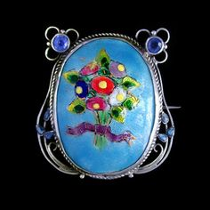 This is not contemporary - image from a gallery of vintage and/or antique objects. GEORGE HUNT (1892-1960)  A silver brooch, set with a central enamel plaque, bordered with wirework flowers  set with blue stones and with blue enamelled leaves.