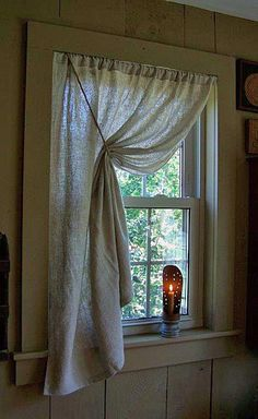 Prim...love the curtains & the tin candle holder on the sill.