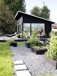 Tuinhuis in zwart gebeitsit hout - plantenbakken in zwartgebeitst hout - grind - beton - gras
