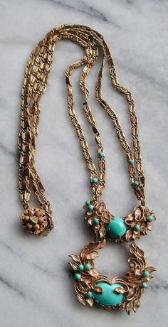 """This necklace has faux turquoise stones which are prong set in a beautiful gold tone metal setting. The setting is covered with small leaves which are hand-wired onto the backing. 13"""" L; falls at the top of the breasts. 