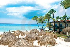 Landscape photo of Aruba's tropical beach with tebts and hotel.