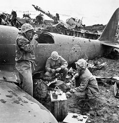 U.S. Marines take a meal break behind the wreckage of a downed Japanese aircraft during a lull in their fierce battle on Iwo Jima — February 1945. (Photo: Eugene Smith, Time/LIFE)