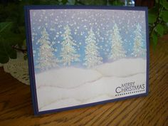 handmade winter/Christmas card ... snowy winter scene with glittery trees and snow drifts ... beautiful colors in the sponged sky with falling snow ...