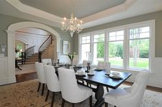 Traditional dining room with sage green paint color, octagon tray ceiling, arched doorway, salvaged wood dining table, white tufted dining chairs, wainscoting and Visual Comfort Lighting Small Faceted George II Chandelier.