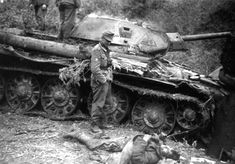 A German soldier examines a knocked out Russian tank & dead crewman. Barbarossa, Russia.