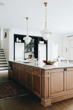 Wood island with dark cabinets, and vintage rug. Oversized wood island with pendant lights in kitchen.