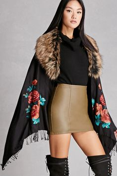 A cashmere-blend poncho by JayLey Collection™ featuring a removable multicolored faux fur trim, embroidered rose design, an open-front with a hidden hook-eye closure, a draped silhouette, and tasseled hem.