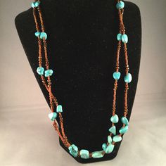 This double strand necklace has burnt orange seed beads with turquoise stones.
