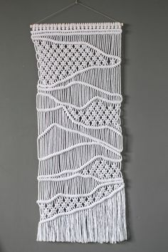 This handmade macrame wall hanging is made using recycled cotton cord. Supporting rod is pine, sanded and painted white. Dimensions -  Height: