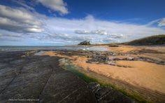 landscape wallpaper of Bamburgh Castle and rock covered beach in Northumberland