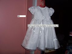 60 cm long newborn gown with bridal satin underlay and organza and pearls skirt with bows and pearls and pearls on chest 1 gown left reduced to $150 comes with hat and bib ring 0427820744