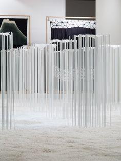 Fragile hemp textiles showcased across banks of metal rods.