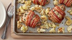 Herbed bacon-wrapped pork chops and lemony roasted cauliflower come together in a simple sheet-pan dinner the whole family will love.