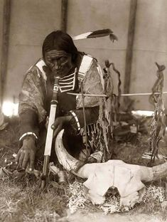 You are looking at a beautiful picture of Saliva, a Sioux Man. It was taken in 1907 by Edward S. Curtis.    The picture presents the man with calumet kneeling by altar inside tipi. He is smoking a pipe.    We have created this collection of pictures primarily to serve as an easy to access educational tool. Contact curator@old-picture.com.    Image ID# 28C74519